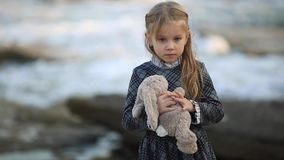 Little sad girl with blond hair stands against the sea on a very windy day. Girl playing with a toy hare and a soft teddy bear. Little cute girl with blond hair stock video