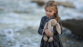 Little sad girl with blond hair stands against the sea on a very windy day. Girl playing with a toy hare and a soft teddy bear. Little cute girl with blond hair stock footage