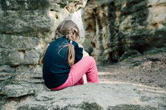 Little sad girl. Crying sitting on a rock, view from behind Royalty Free Stock Photography