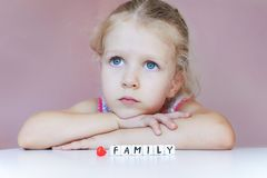 Little sad girl dream about family. Protect your family concept. With hands on chin looking up. Word Family made of plastic blocks Stock Photo