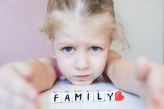 Little sad girl dream about family. Protect your family concept. Little sad girl looking at camera dream about family. Protect your family concept. Word Family Royalty Free Stock Photo