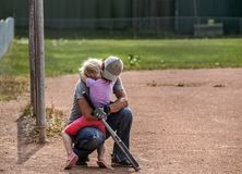 Little sad girl getting a big hug. An uncle wearing a hat and baseball gloves kneeling down and giving his neice a comforting hug at a baseball diamond Royalty Free Stock Images