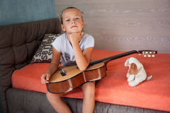 Little sad girl with a guitar. On his knees looking into the frame Stock Image