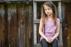 Little sad girl with headphones sitting on a wooden stepladder in the village. Outdoors Royalty Free Stock Photos