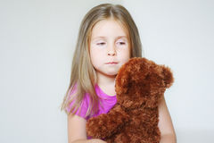 Little sad girl hugging a teddy bear. At home Royalty Free Stock Images
