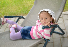 The little sad girl lies in a chaise lounge.  Stock Images