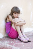 Little sad girl with long hair sitting hugging her knees. Leaning against the wall Stock Images