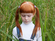 Little sad girl lowered her eyes. Portrait close-up on a background of green grass Stock Photography