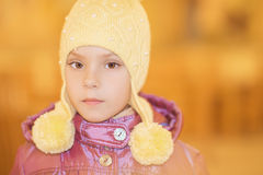 Little sad girl in pink coat. And yellow cap Royalty Free Stock Images