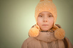 Little sad girl in pink coat. And yellow cap Stock Photography