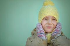 Little sad girl in pink coat. And yellow cap Stock Photos