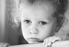 Little sad girl on the playground. Black and white series Stock Image