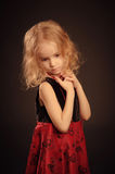 Little sad girl portrait. Little sad girl with curly blond hair in red and black dress Royalty Free Stock Photos