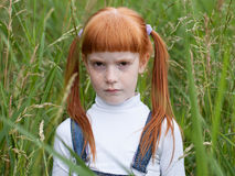 Little sad girl with a puffed cheeks Stock Photography