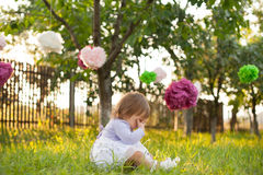 Little sad girl. Seatted on the grass in the garden, decorated with pompoms Royalty Free Stock Images