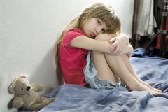 Little sad girl sitting on the bed Royalty Free Stock Photography