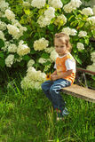 Little sad girl sitting. On bench in flowered Park Royalty Free Stock Image
