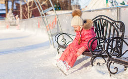 Little sad girl sitting on a bench in the skating. Rink. This image has attached release Royalty Free Stock Photo