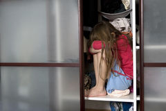 Little sad girl sitting inside wardrobe Stock Images