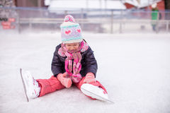 Little sad girl sitting on skating rink after the. Little sad girl sitting on a skating rink after the fall Royalty Free Stock Images