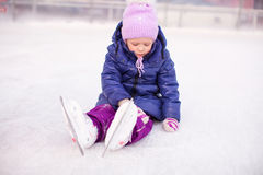 Little sad girl sitting on a skating rink after Royalty Free Stock Photo