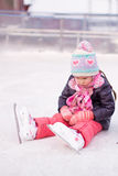Little sad girl sitting on a skating rink after Stock Photo