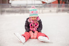 Little sad girl sitting on a skating rink after Stock Image