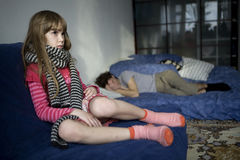 Little sad girl sitting on the sofa. Her father sleeping. Father and daughter Stock Photo