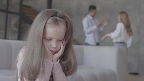 Little sad girl sitting on the sofa in the foreground with her head on hands while african ameican father and caucasian. Little sad girl sitting on the sofa in stock video