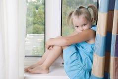 Little sad girl sitting on the windowsill.  Royalty Free Stock Images