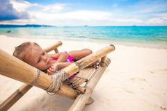 Little sad girl sitting on a wooden chair on the. White beach. This image has attached release Royalty Free Stock Images