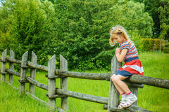 Little sad girl sitting on wooden fence Royalty Free Stock Image