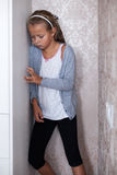 Little sad girl standing in the corner. Of the room Stock Image