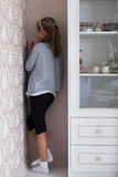 Little sad girl. Standing in the corner of the room Stock Photos