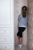 Little sad girl. Standing in the corner of the room Royalty Free Stock Images
