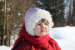 Little sad girl stands in winter forest Royalty Free Stock Images