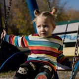 Little sad girl on a swing in the park. royalty free stock image