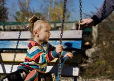 Little sad girl on a swing in the park. royalty free stock photo