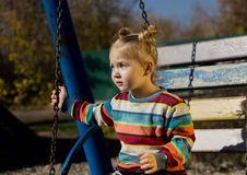 Little sad girl on a swing in the park. royalty free stock photos