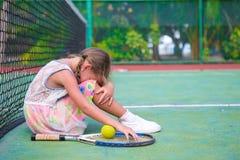 Little sad girl on tennis court Royalty Free Stock Photos