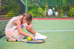 Little sad girl on tennis court Stock Photos