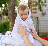 Little sad girl is wrapped up in a white towel. The little sad girl is wrapped up in a white towel Royalty Free Stock Photos