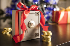 Little safe with red ribbon and golden coins Stock Photography