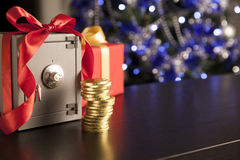 Little safe with red ribbon and golden coins. On background of christmas tree Royalty Free Stock Images