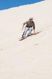 Little Sahara. Sandboarding at sand dunes in Little Sahara, Kangaroo Island, South Australia.Focus on the man royalty free stock image