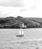 little sailing boat in front of falmouth light house Royalty Free Stock Image