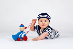 Little sailor. A small boy in prone position with sailerdress and a wood duck Stock Photo