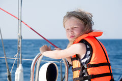Little sailor. Little girl in life jacket sitting on the deck of yacht and looking at camera Royalty Free Stock Photography