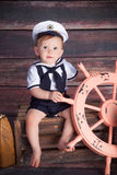Little Sailor. A baby / toddler dressed as a sailor on a wood background royalty free stock image
