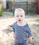 The little sailor with a blond hair. He stays with the grandmother and the grandfather in the village royalty free stock image